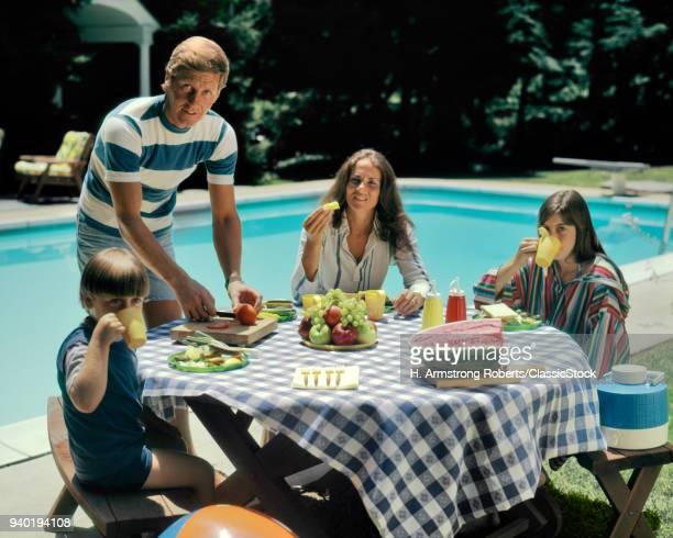 1970s FAMILY BACKYARD SWIMMING POOL EATING FRESH FRUIT PICNIC MAN WOMAN BOY GIRL LOOKING AT CAMERA