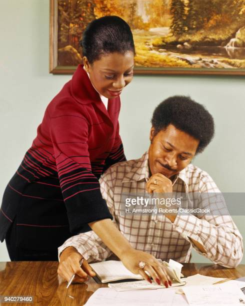 1970s SMILING AFRICAN AMERICAN COUPLE AT TABLE WRITING CHECKS PAYING BILLS