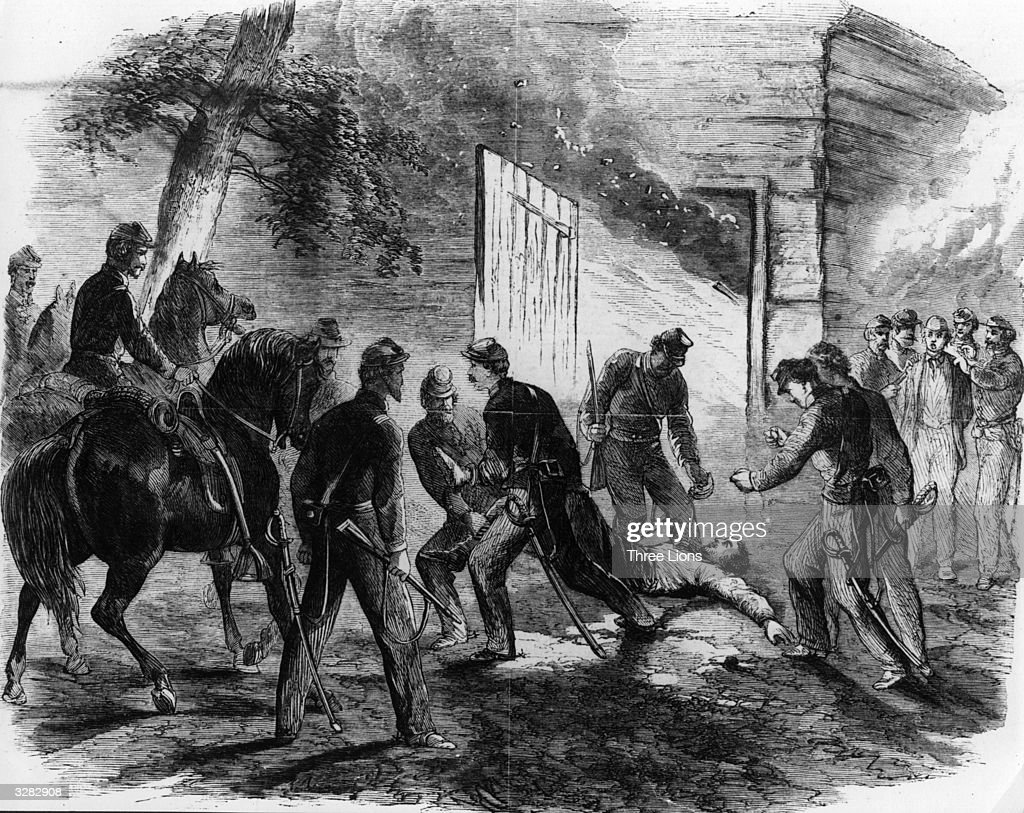 John Wilkes Booth being dragged from the barn on Garretts farm by Union cavalry sent to capture him after his assassination of President Lincoln.