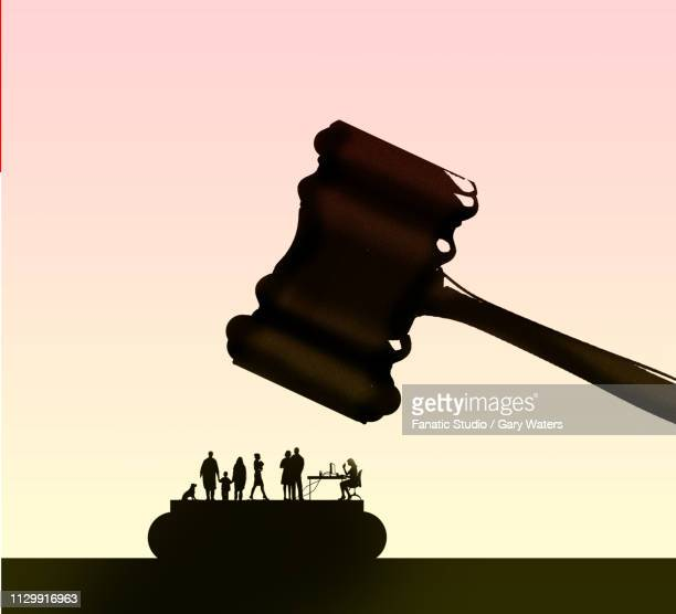 a concept image of a gamel coming down on a group of people representing injustice in society - unfairness stock illustrations