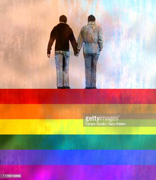 a concept image of two men holding hands standing on an lgbtq flag depicting happy gay relationship.