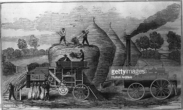 Agricultural workers use a steam powered thresher that looks like an early locomotive.