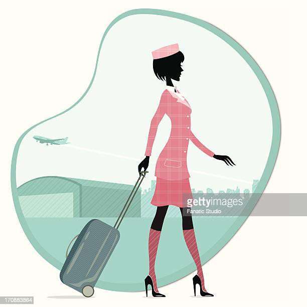 Air hostess walking with luggage at an airport