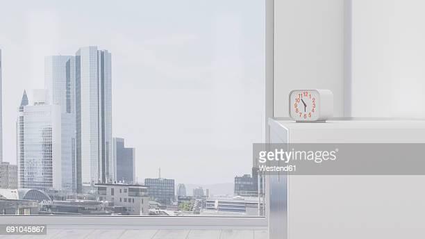 Alarm clock on sideboard in front of urban skyline, 3d rendering