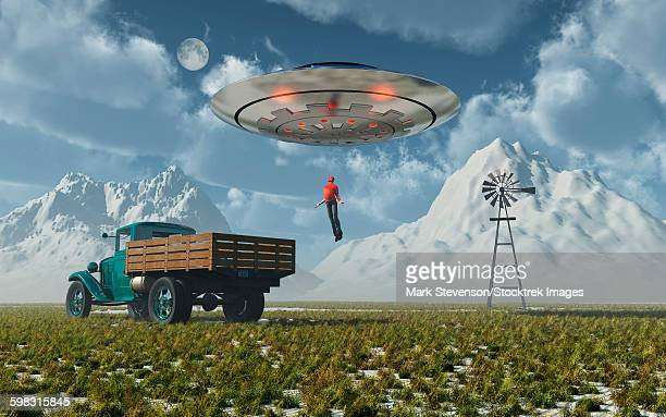Aliens abducting a man into a flying saucer.