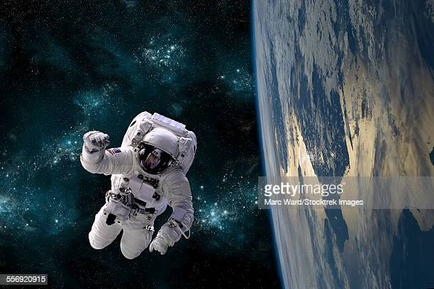 An artists depiction of an astronaut floating in space while orbiting a large, Earth-like planet.