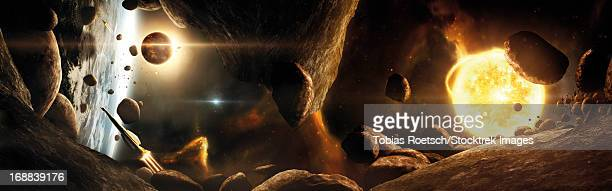 an asteroid field next to an earth-like planet in a dual-star system. - next stock illustrations