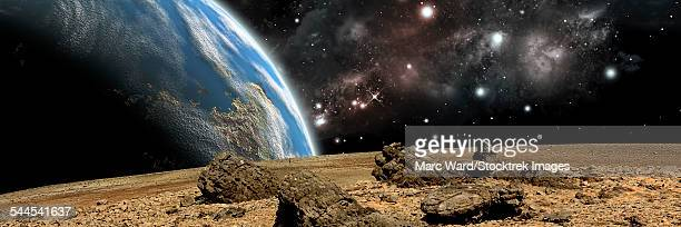 An Earth-like planet rises over a rocky and barren alien world.