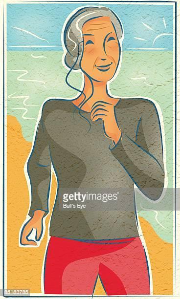An elderly woman jogging at the beach