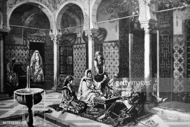 Arab women play cards at the court of the oriental residence _ 1895