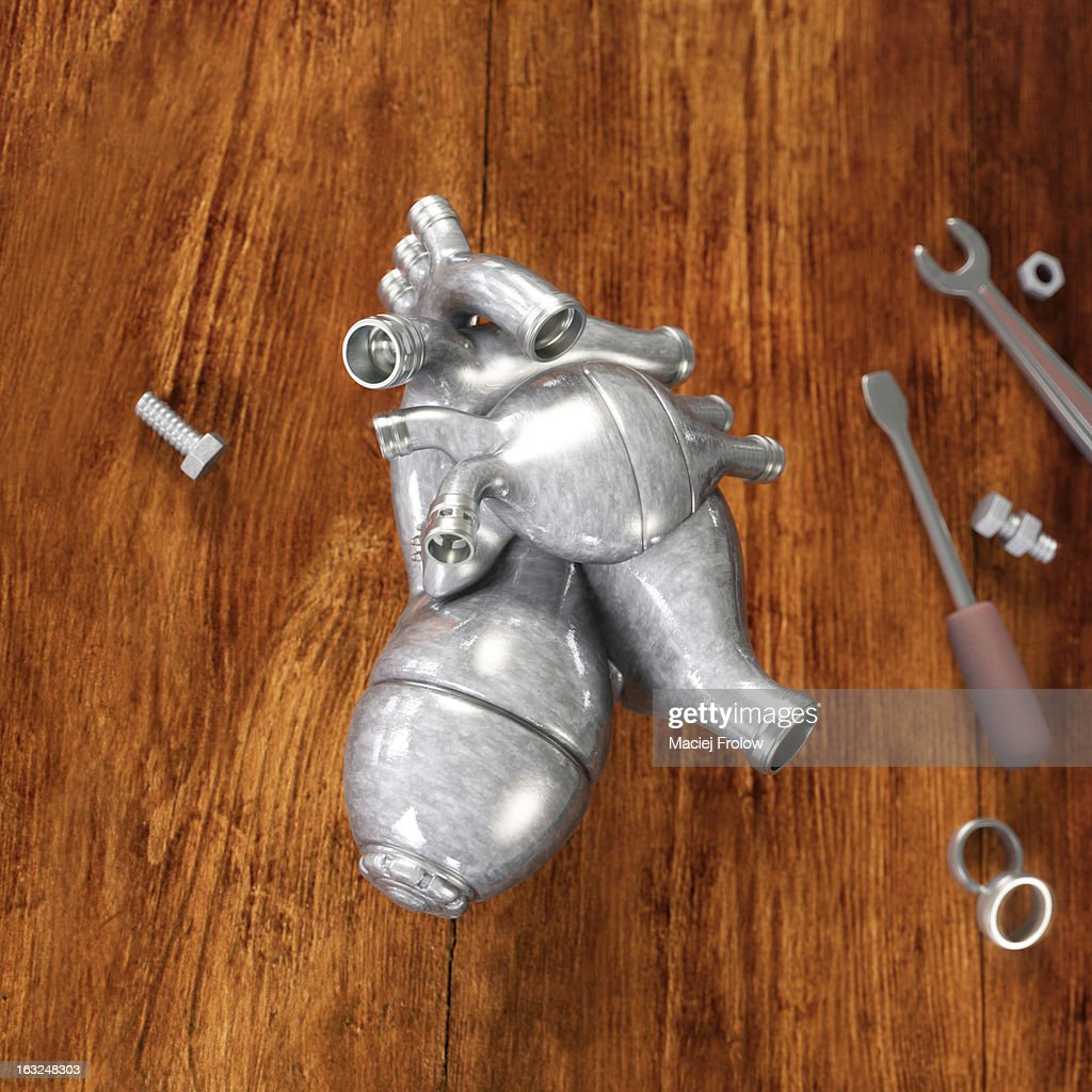 Artificial heart made of metal on wooden table : Stock Illustration