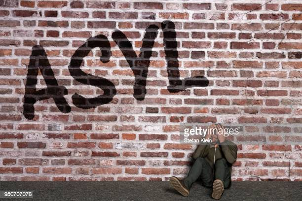 asylum seeker sitting in front of a wall with writing asylum, his head in his hands, computer graphic - klein stock illustrations
