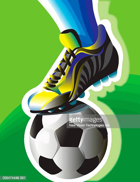 Athlete standing with foot atop soccer ball, low section