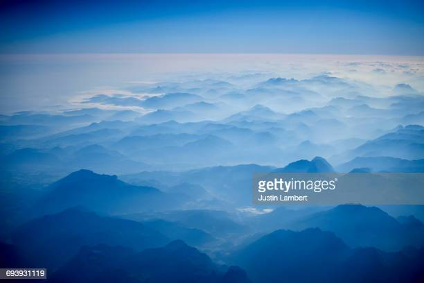 austrian alps from a plane window in morning - ethereal stock illustrations, clip art, cartoons, & icons