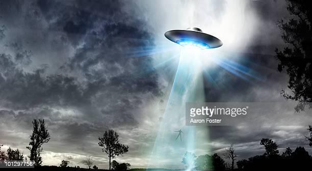 ufo beaming up a man - conspiracy stock illustrations