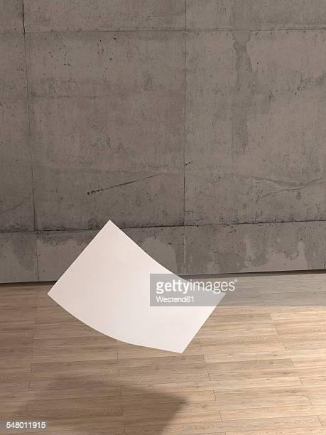 Blank sheet of paper falling to wooden floor
