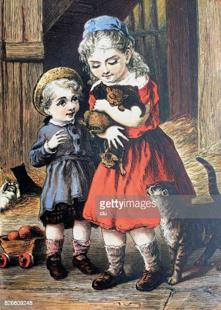 Blond girl in barn holding the cats babies in her arms