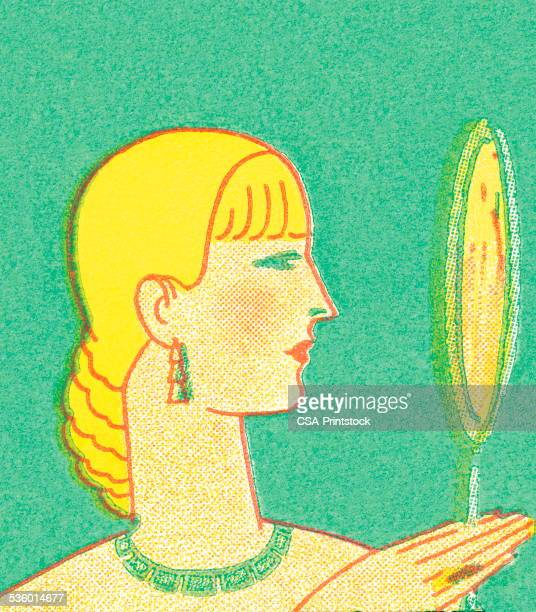 Blond woman looking in hand mirror