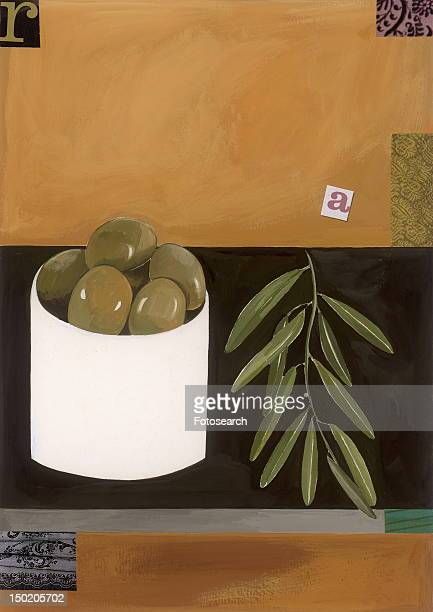 A bowl of green olives with an olive branch