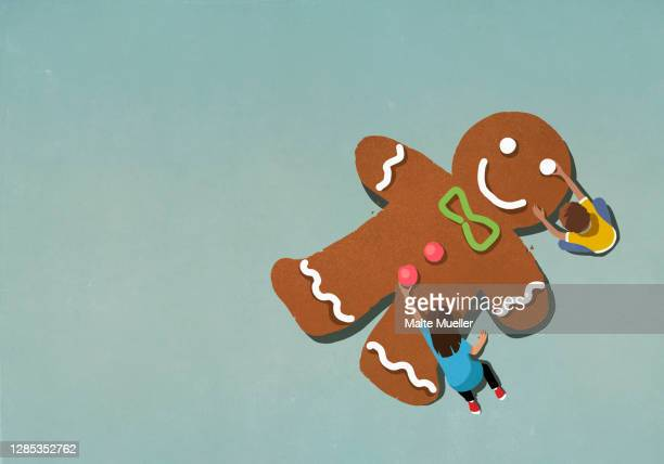 boy and girl assembling gingerbread man - scale stock illustrations