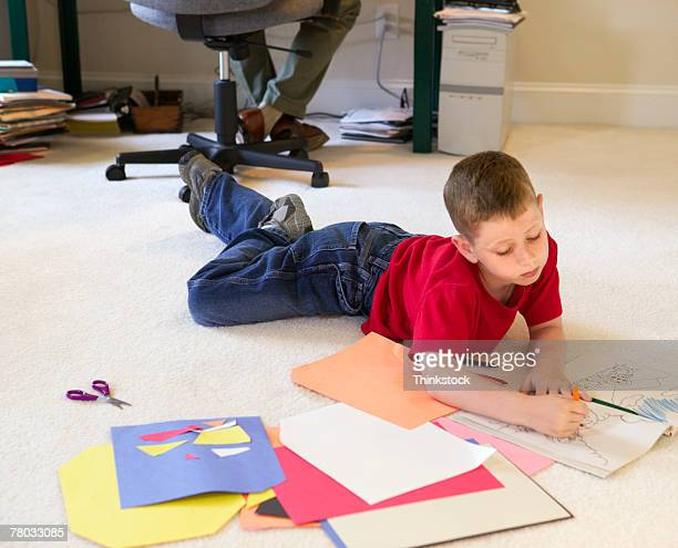 a boy colors among papers on the floor as his dad works at his desk in the background - 大人点のイラスト素材/クリップアート素材/マンガ素材/アイコン素材