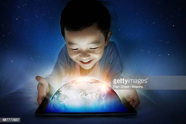 a boy looking at the earth on the tablet in the duvet - all shirts stock-grafiken, -clipart, -cartoons und -symbole