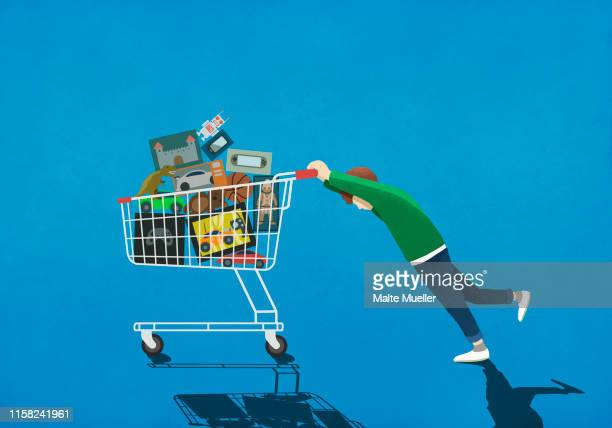 boy pushing shopping cart full of toys - consumerism stock illustrations
