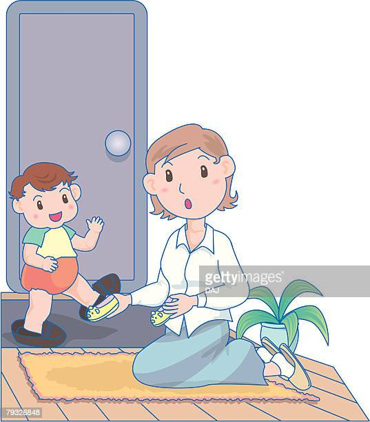 boy putting on fathers shoes in entrance - japanese mom stock illustrations, clip art, cartoons, & icons