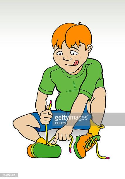 Boy's tying his shoes.