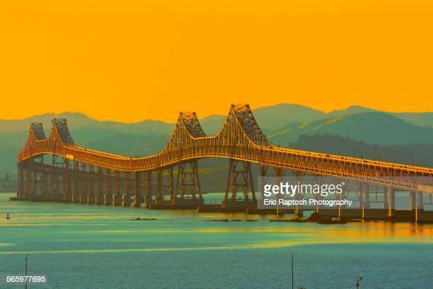 bridge and river under sunset sky, richmond, california, united states - san rafael california stock illustrations