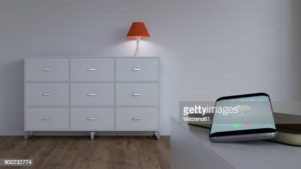 Burning lamp on sideboard and smartphone with control app