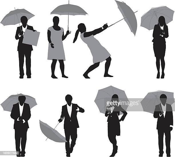 Business executives with umbrellas
