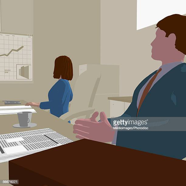 Businessman and a businesswoman looking at a projection screen
