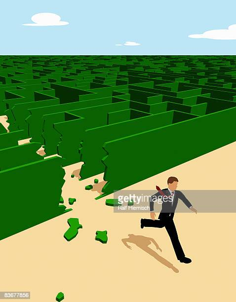 A businessman breaking through the walls of a maze