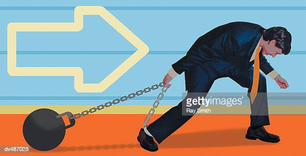 Businessman dragging ball and chain