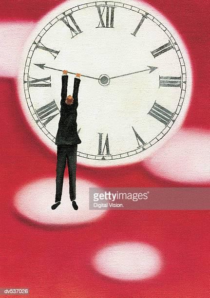 Businessman hanging onto a clock