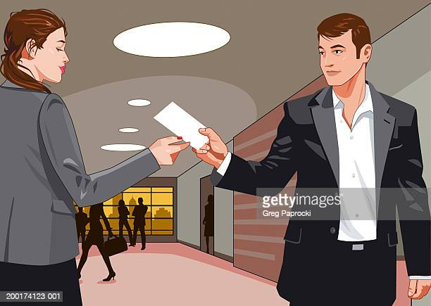 Businessman passing note to businesswoman in office hallway