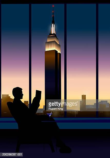 Businessman relaxing in chair, city skyline in background, dusk