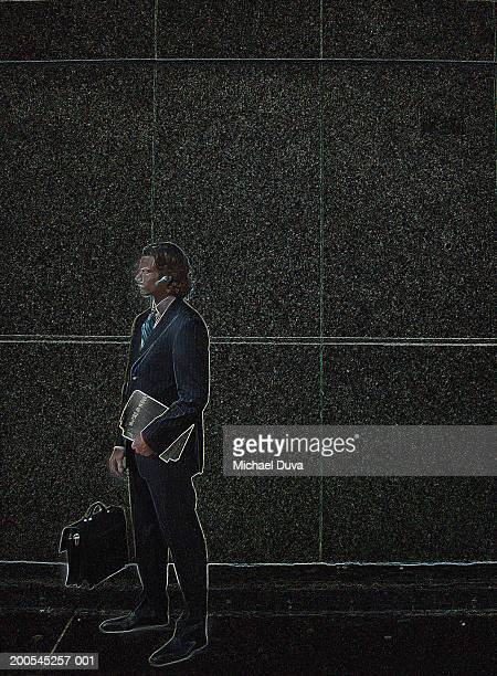 businessman standing against wall holding file, side view - digital enhancement stock illustrations