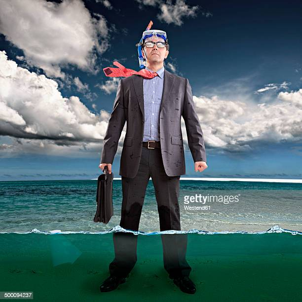 Businessman standing ankle-deep in water, wearing snorkel
