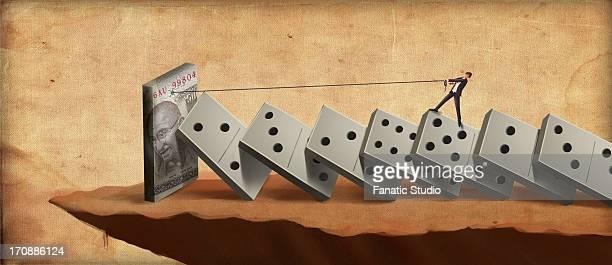 businessman standing on dominoes struggling for money - domino effect stock illustrations
