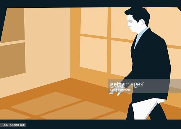 Businessman walking across room,  profile