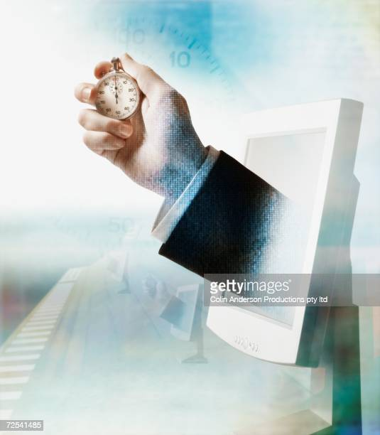 businessman's hand emerging from computer monitor and holding stopwatch - deadline stock illustrations