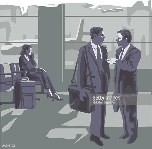 Businessmen talking in airport terminal