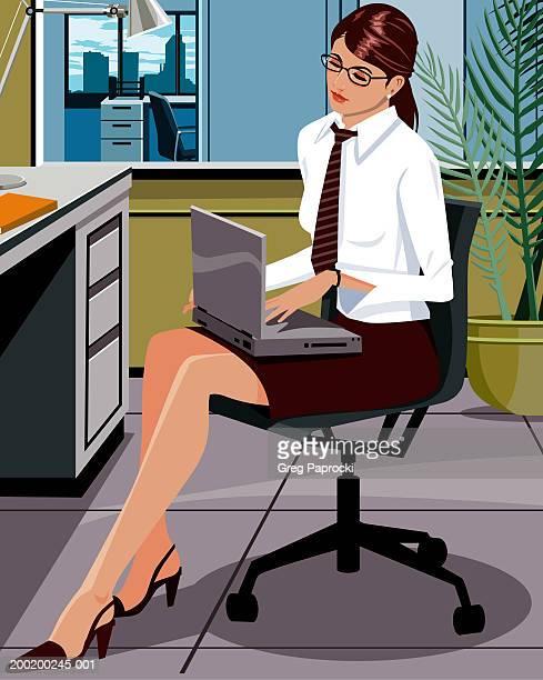 Businesswoman sitting at desk, using laptop