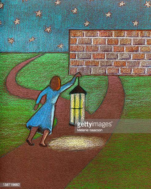 A businesswoman using a lantern to light her way along a path