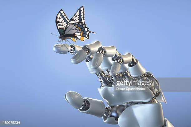 Butterfly standing on fingertip of a robot hand