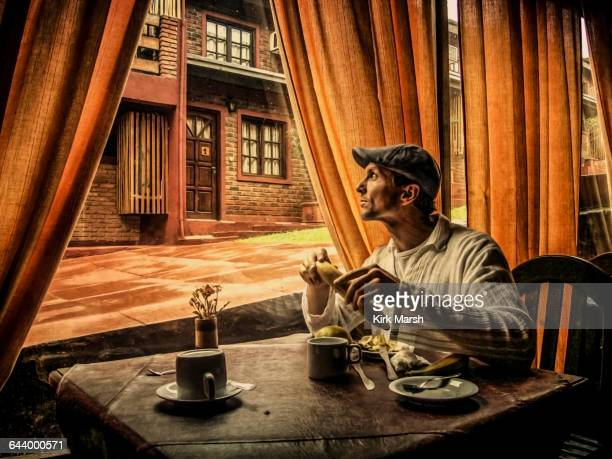 Caucasian man eating in cafe