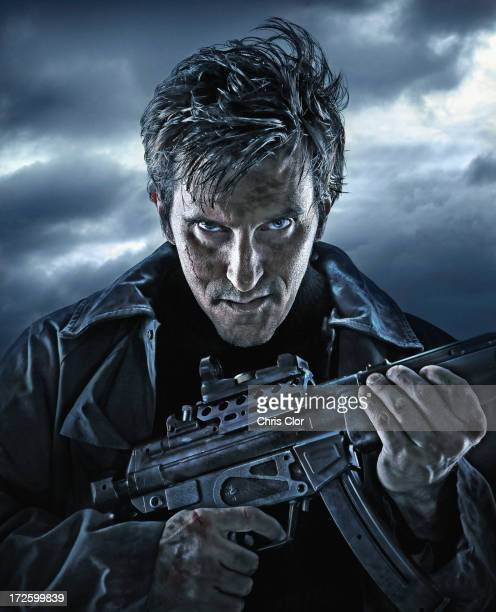 Caucasian man holding machine gun outdoors