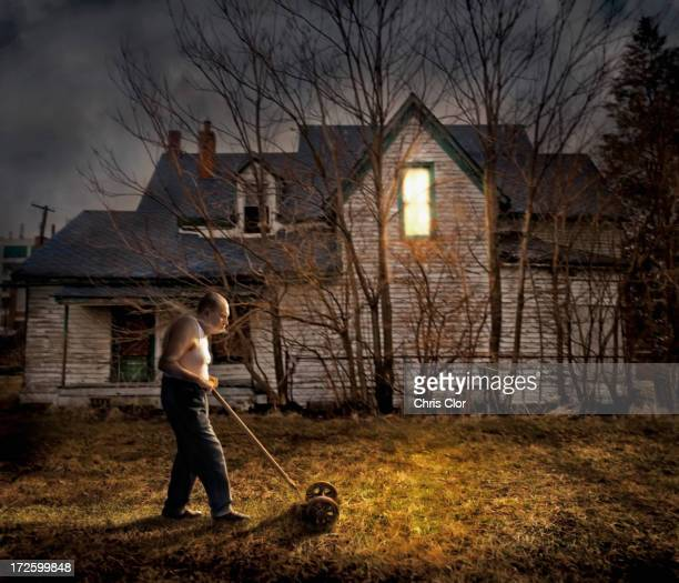 Caucasian man mowing lawn outside home